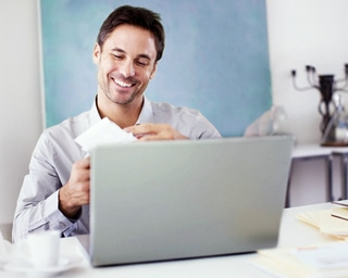 Small image of a man sitting behind laptop looking at envelopes