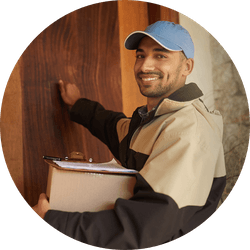 Delivery man wearing hat knocking on door carrying box and clipboard