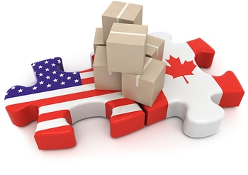 A bundle of packages set atop joined U.S.A. and Canadian flag puzzle pieces.